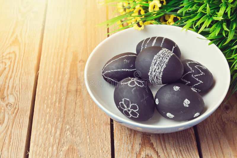 Easter eggs painted with chalkboard paint on wooden background. Easter eggs painted with chalkboard paint on wooden vintage background stock photos