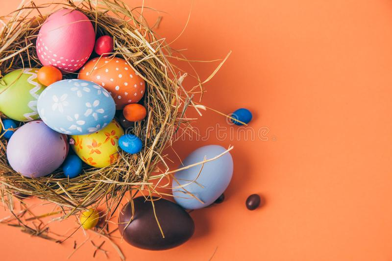 Colorful easter eggs with chocolate and candies in a nest on a orange background royalty free stock photo