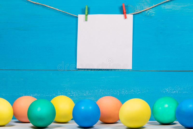 Easter eggs painted in different Colors on blue background with place for inscription on white paper stock image