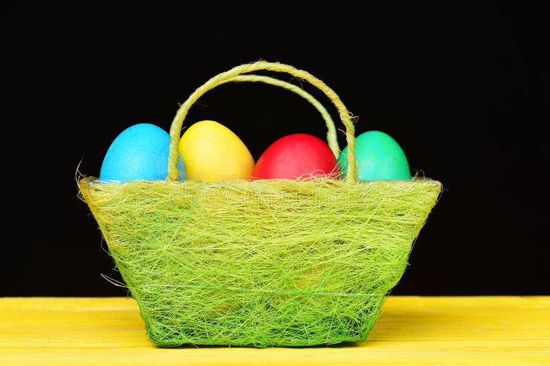Easter eggs painted in different colours in light basket stock photo
