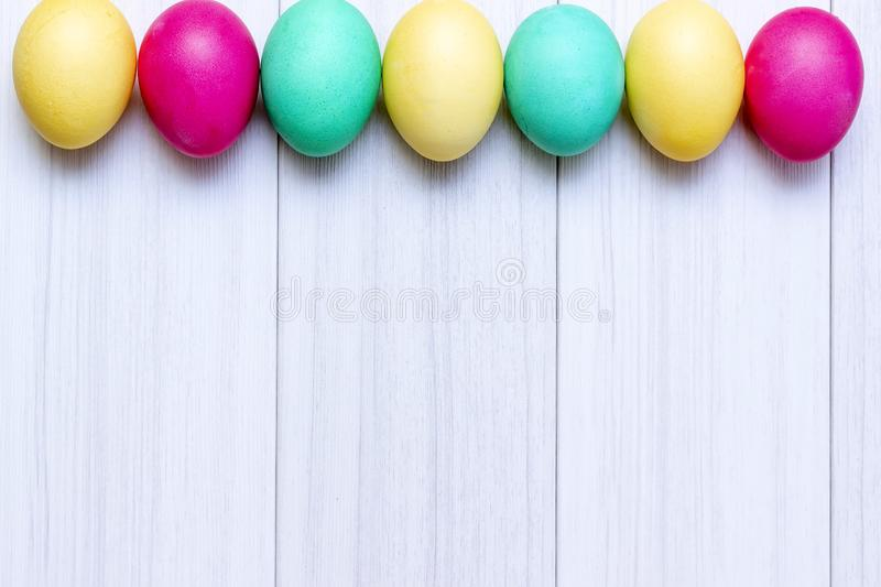 Easter eggs painted in pastel colors on a white wooden background royalty free stock photos
