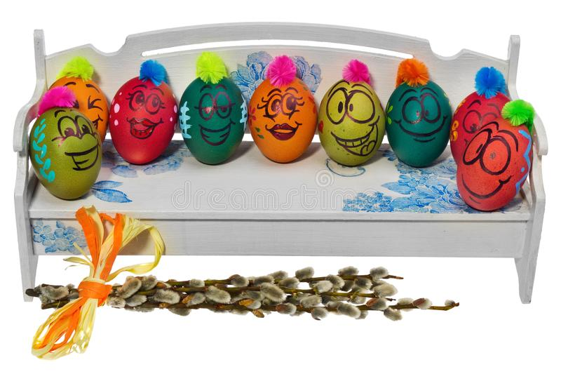 Easter eggs painted in smiling cartoon faces are sitting on a wooden bench. Decorated eggs with funny colorful hairstyles. royalty free stock image