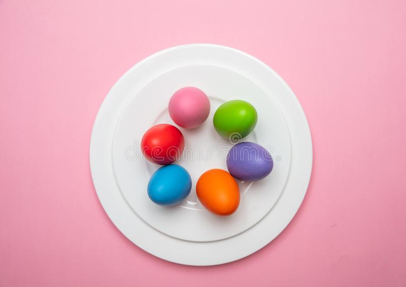 Easter eggs, pastel colors painted in a white plate, pink color background stock images