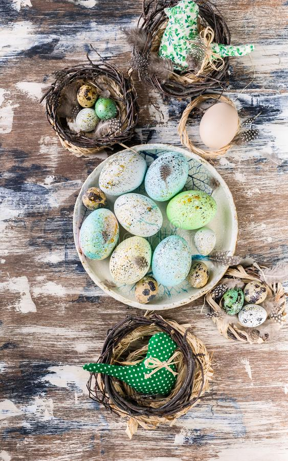 Easter eggs on a plate and in a small nest on colorful surface. Vertical shot royalty free stock photo