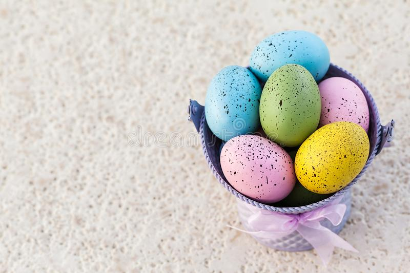 Easter eggs in a purple bucket for traditional holiday with copy space on the left. Image stock images