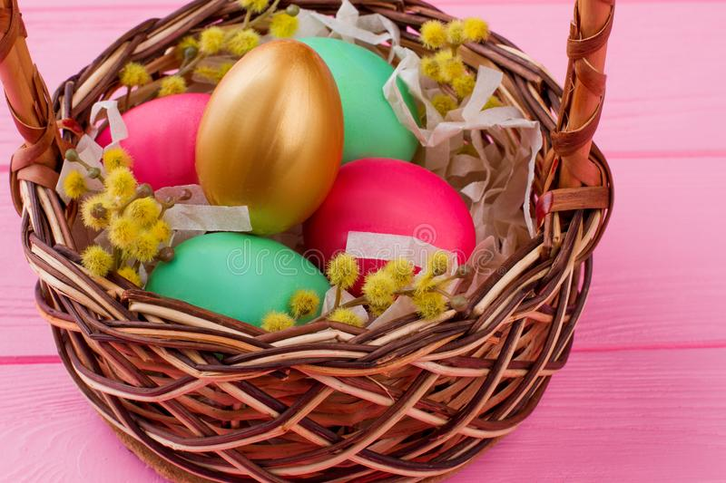 Easter eggs and pussy-willow in woven basket. royalty free stock images