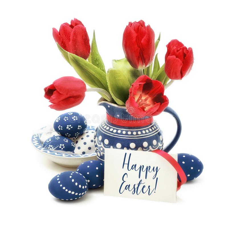 Easter eggs and red tulips in blue ceramics on white, text royalty free stock photo