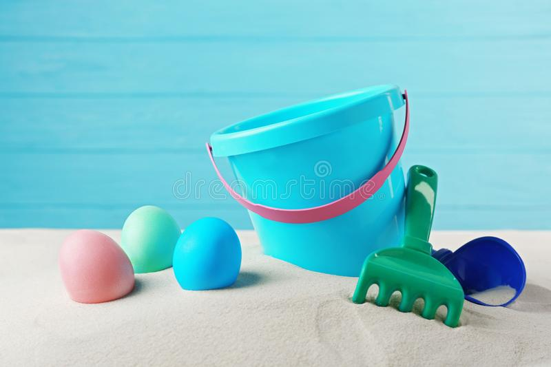 Easter eggs with sand and pail,. On wooden blue background royalty free stock photos