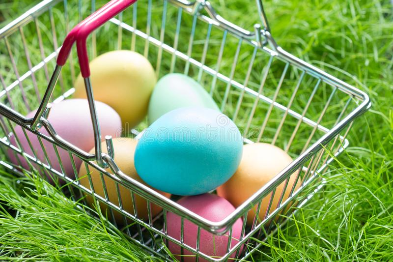Easter eggs in a shop basket on the grass. Shopping background stock photography