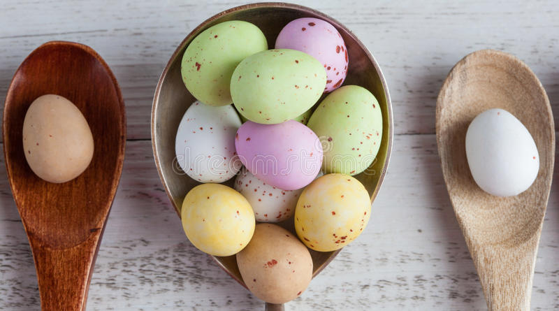 Easter eggs - speckled and sugar coated on wooden and silver spoons on white rustic wooden table, top view extreme closeup. royalty free stock photography