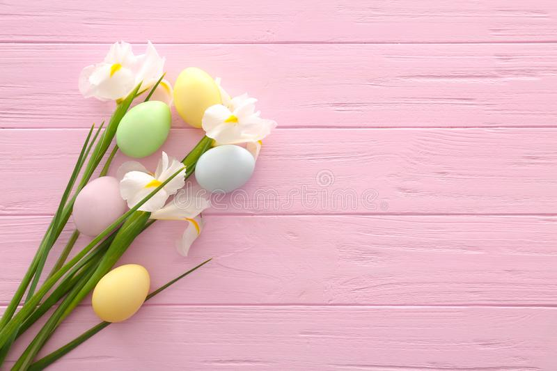 Easter eggs with spring flowers on color wooden background royalty free stock photo