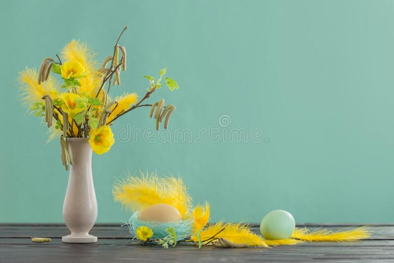 Easter eggs and spring flowers on green background. The Easter eggs and spring flowers on green background stock image