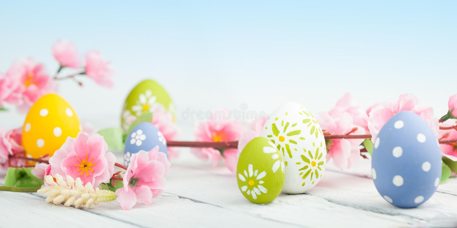 Easter eggs with spring flowers. On wooden table stock photo