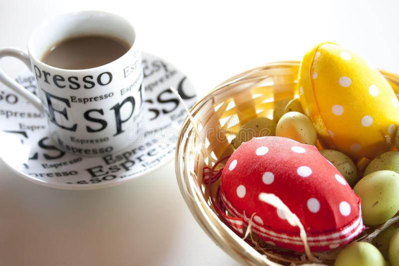 Easter eggs on the straw in a basket and a cup of coffee on a white table. Easter decorations. royalty free stock image