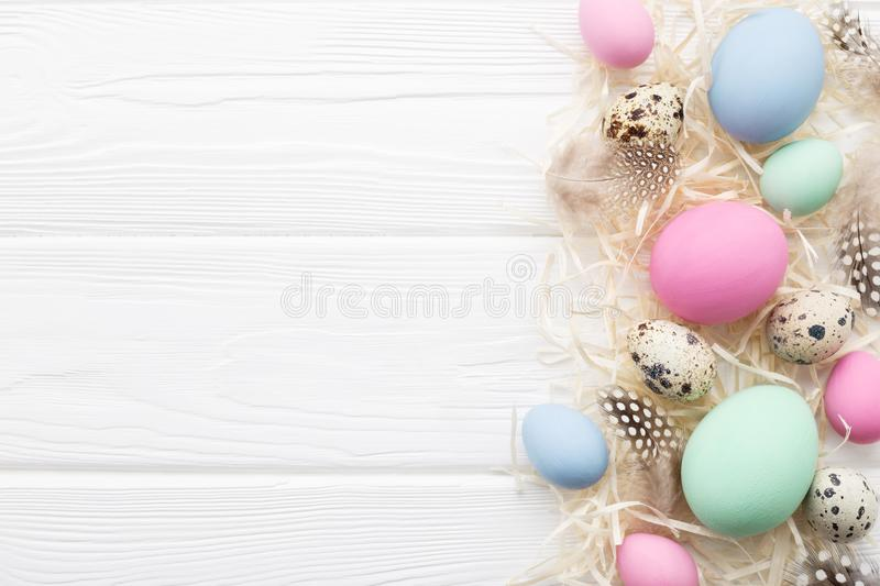 Easter frame with pastel colored eggs on white wooden table stock photo