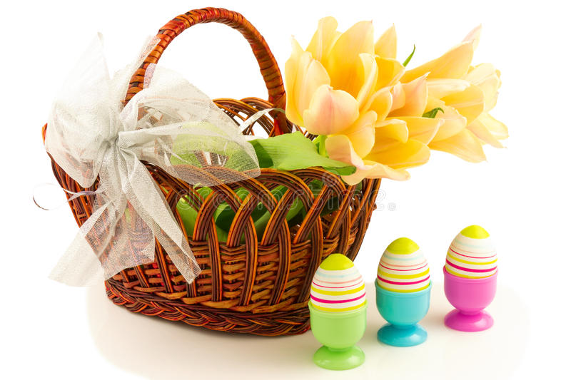 Easter eggs, tulips in basket with bow royalty free stock photos