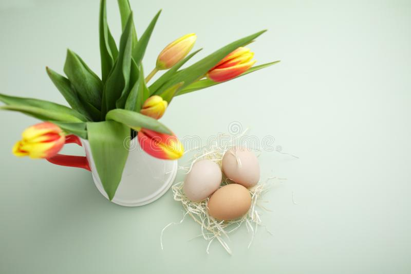 Easter eggs and bouquet of tulips on green background stock photography