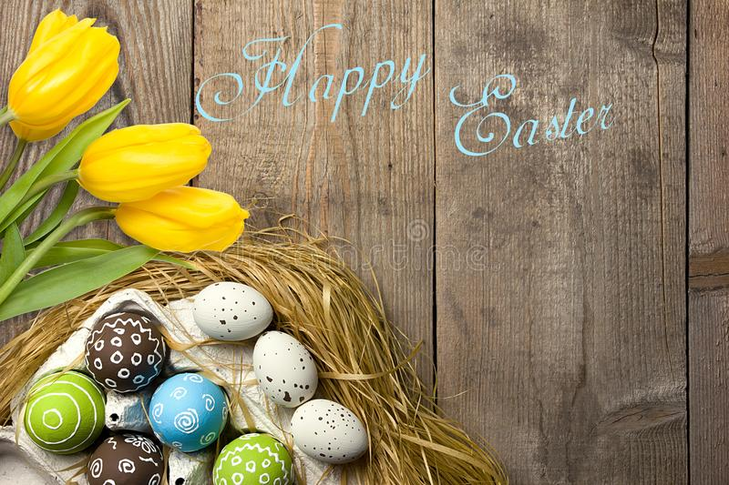 Easter card with colorful eggs in nest and yellow tulips over wooden background. Top view with copy space stock photography