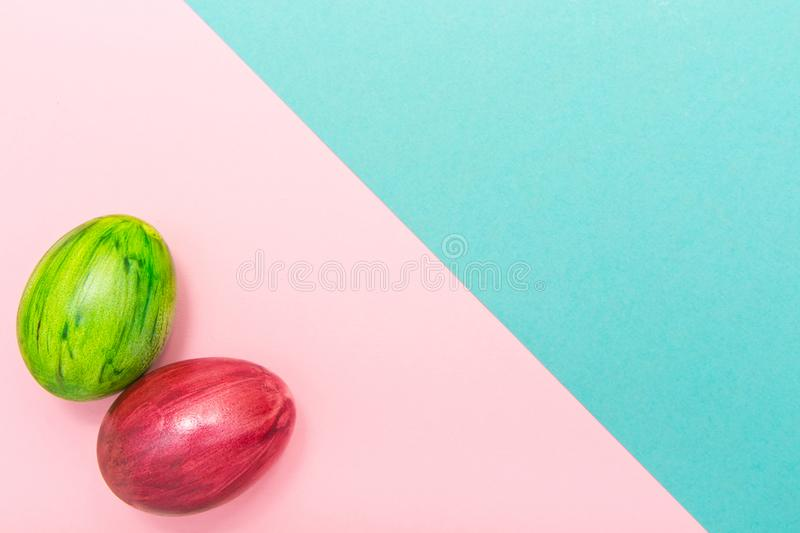 Easter Eggs on turquoise and pink geometric background. Green and red egg handmade new style of colouring on a colored cardboard. royalty free stock image