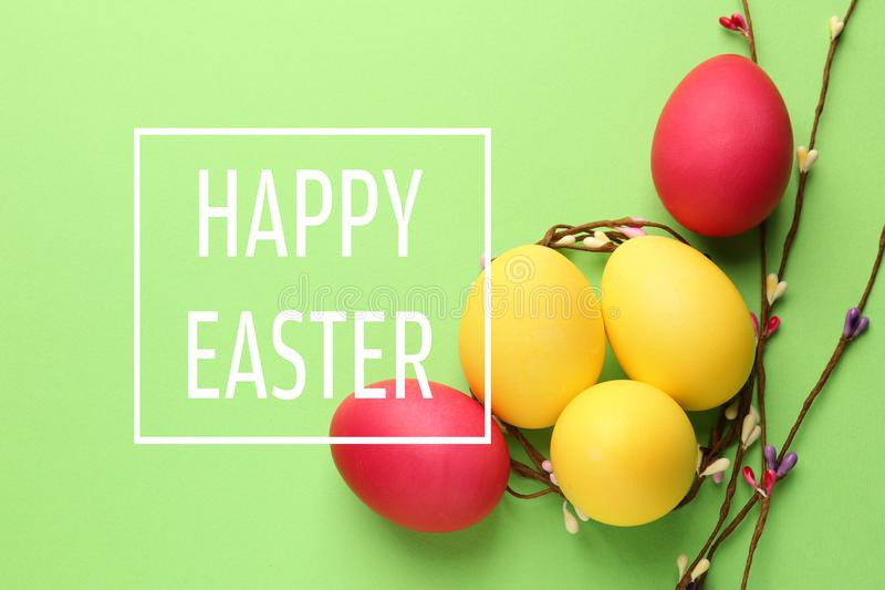 Easter eggs with twigs on color background royalty free stock photo