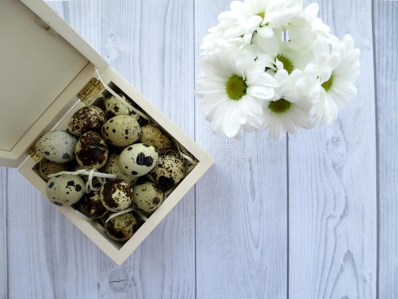 Easter eggs and white flowers on a white wooden table royalty free stock image
