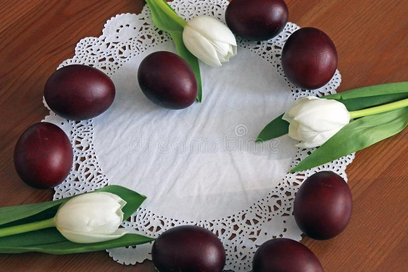 Easter eggs and white tulips on the table laid out in the shape of a heart stock image