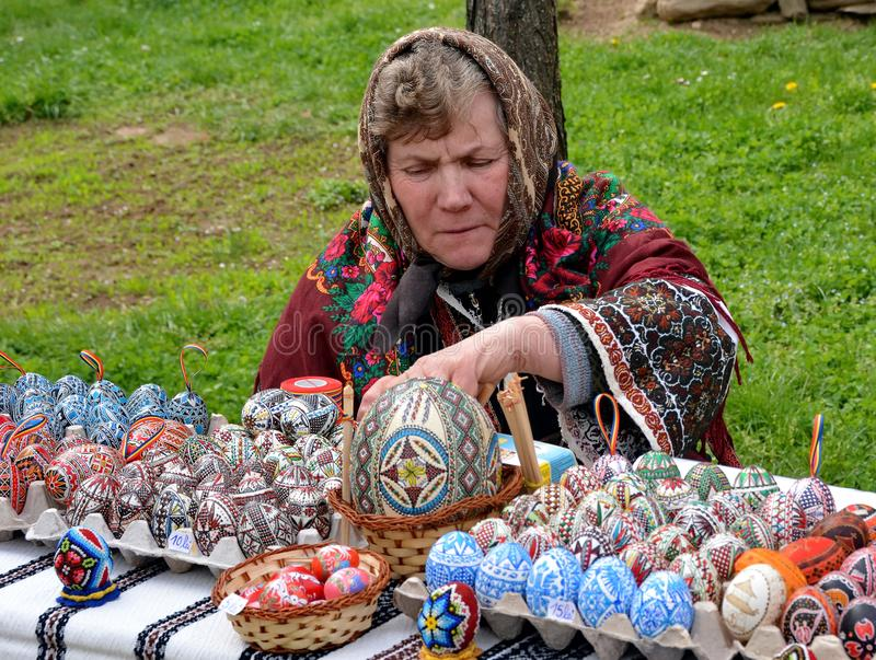 Romania Easter Eggs. Woman painting and selling traditional painted Romanian Easter eggs in Romania royalty free stock photos
