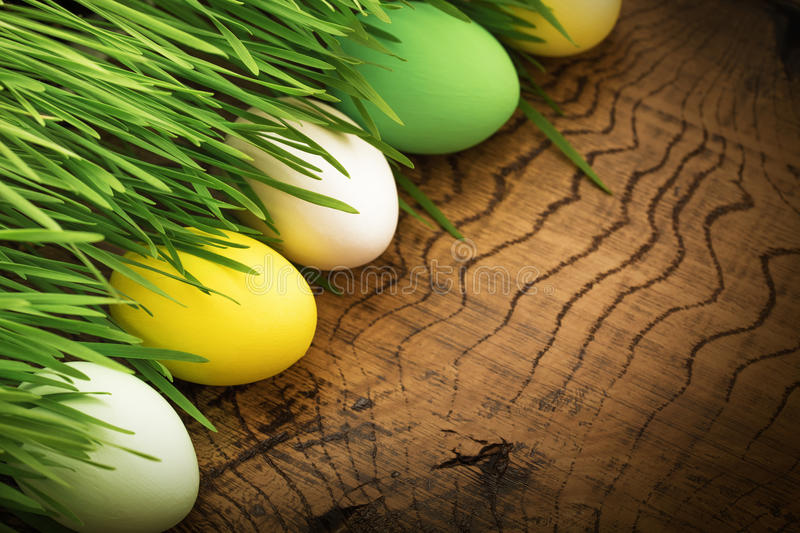 Easter eggs on wood background. Easter eggs with green grass on wood background royalty free stock photography