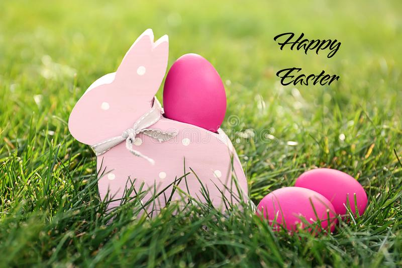 Easter eggs with wooden bunny toy on green grass outdoors stock photo