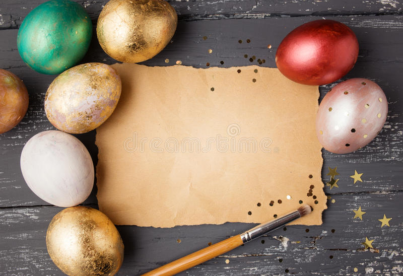 Easter eggs on wooden table with blank paper for text. royalty free stock photography