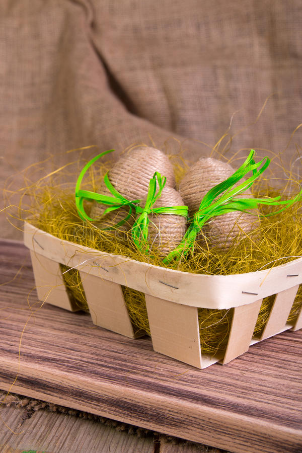 Easter eggs wrapped in twine in yellow nest on wooden sackcloth wooden background. Rustic style. Easter eggs wrapped in twine in yellow nest on wooden sackcloth stock photos