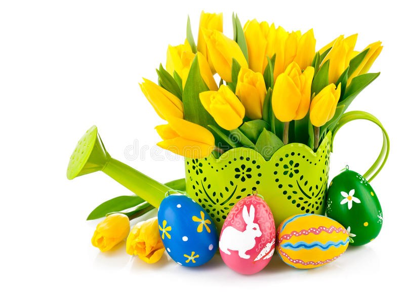 Easter eggs with yellow tulips in watering can stock images