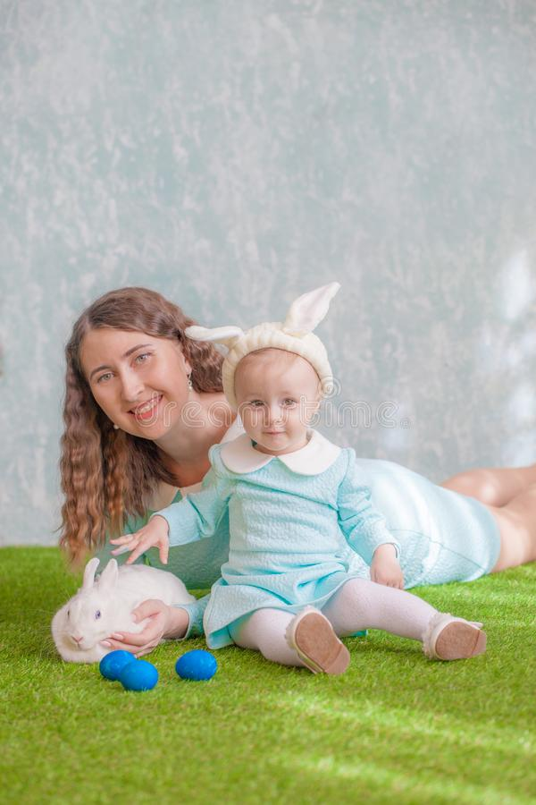 Easter. Family with easter bunny on green grass. With blue eggs. mother and daughter petting a hare. vertical sheet orientation royalty free stock photography