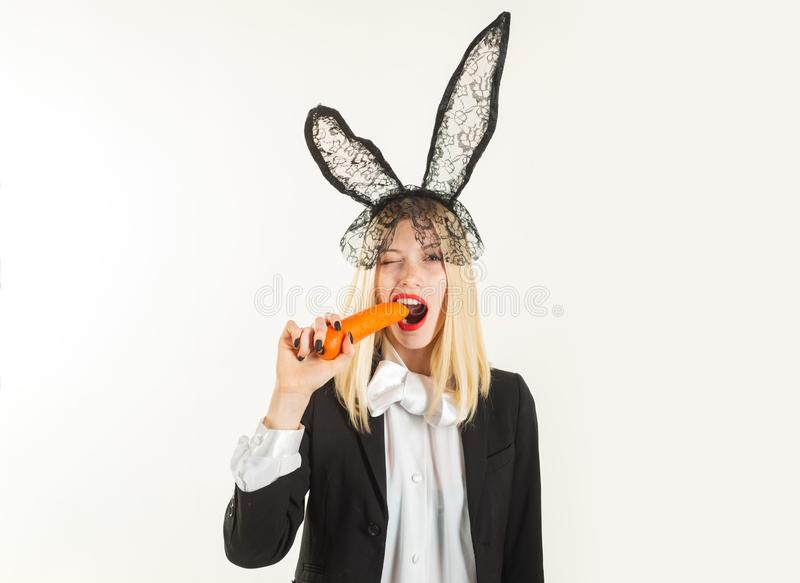 Easter feliz Coelhinho da Páscoa 'sexy' que come a cenoura Mulher sensual que veste as orelhas de coelho pretas da Páscoa do laço imagem de stock