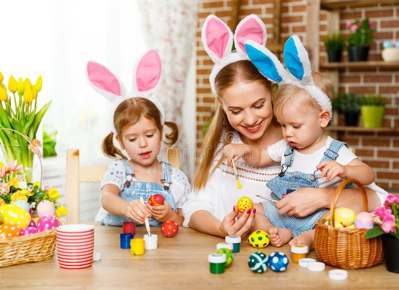 Easter feliz! a mãe e as crianças da família pintam ovos para o feriado fotografia de stock royalty free