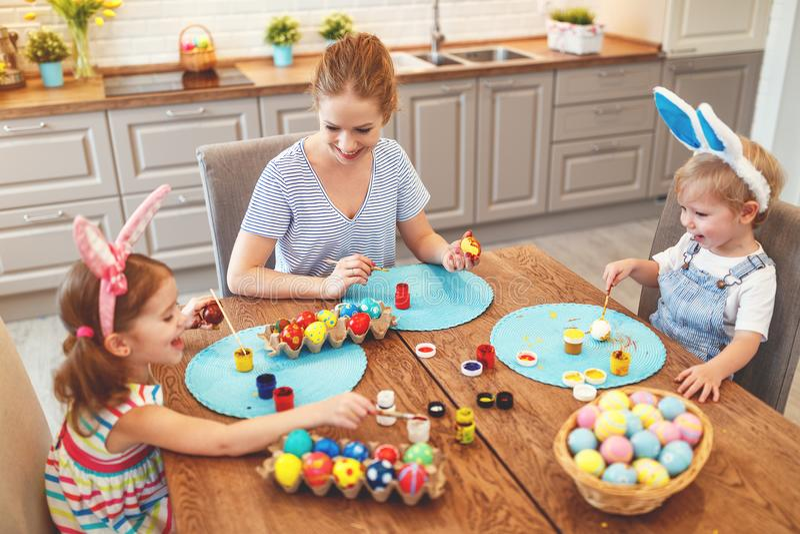 Easter feliz! a mãe e as crianças da família pintam ovos para o holida imagem de stock