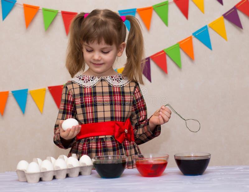Easter feliz O pintor da menina pintou ovos Criança que prepara-se para a Páscoa Mão pintada Pintura do dedo Conceito da arte e d foto de stock