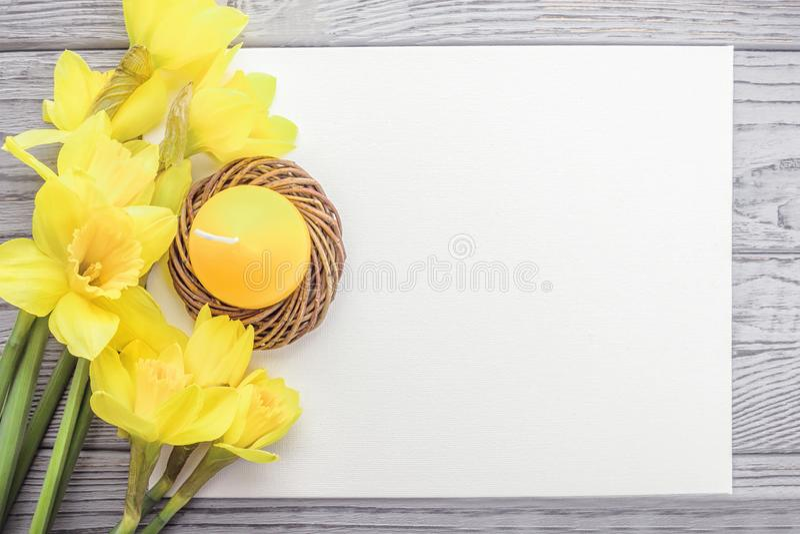 Easter feliz Ovo e narcisos amarelos da vela da Páscoa em um fundo cinzento Copie o espaço, vista superior imagem de stock