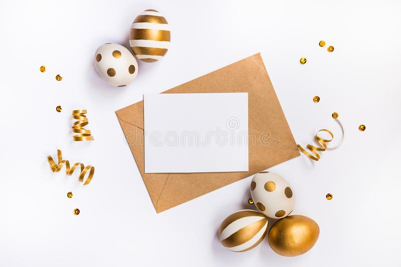Easter festive decoration. Top view of easter eggs colored with golden paint in differen patterns and empty mock-up card in a kraf. T envelope. Various striped stock images