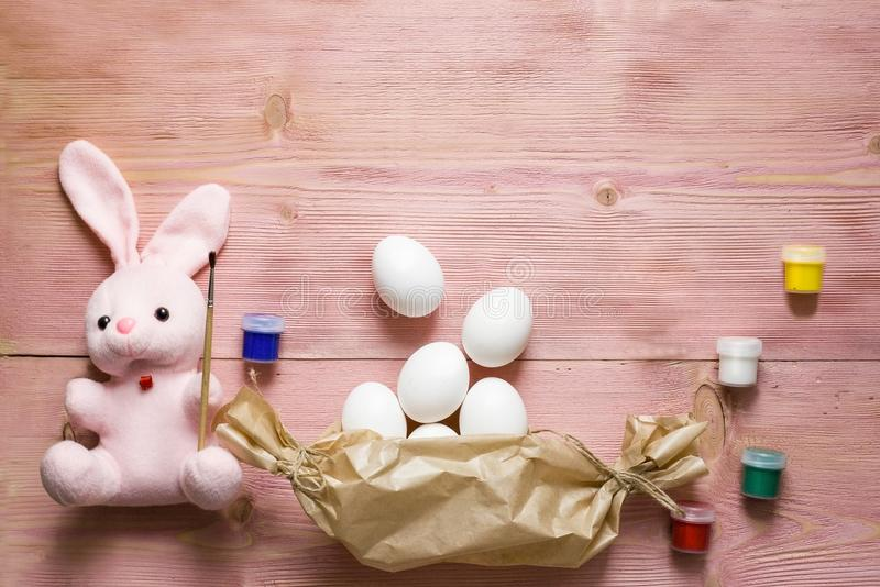 Easter festive set with eggs, flower and easter rabbit, paint, brush, wrapping paper on rustic wooden table with copyspace. Flat l royalty free stock photo