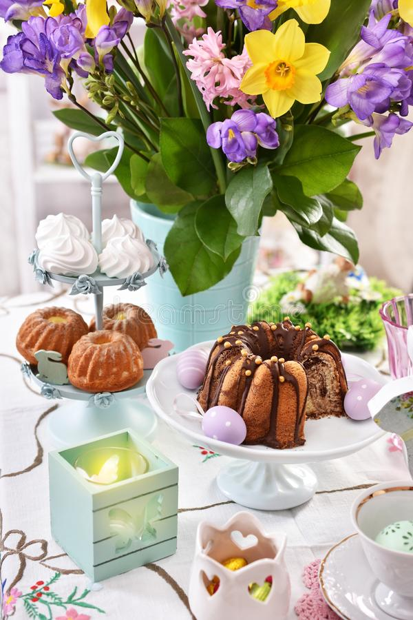 Easter festive table decoration with spring flowers and pastries stock images