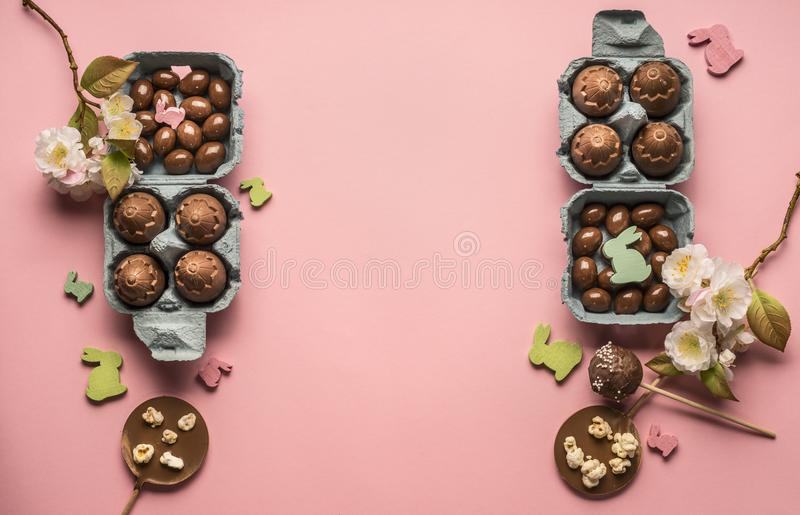 Easter flat lay chocolate eggs various decorations, wooden rabbits and birds greeting card, on pink background, space for tex stock photo