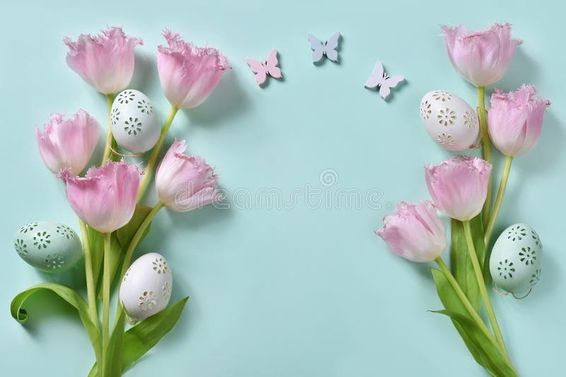 Easter flat lay with pink tulips and eggs on mint background royalty free stock images