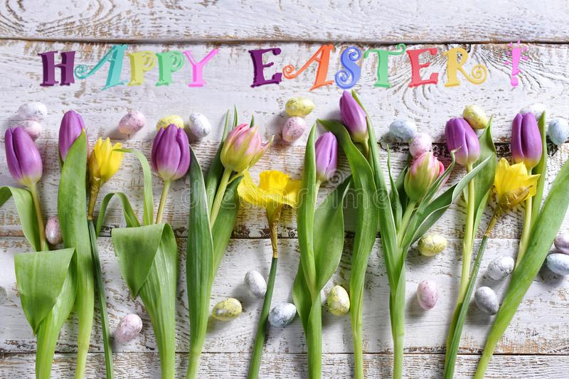 Easter flat lay with a row of colorful flowers eggs and wishes text stock image