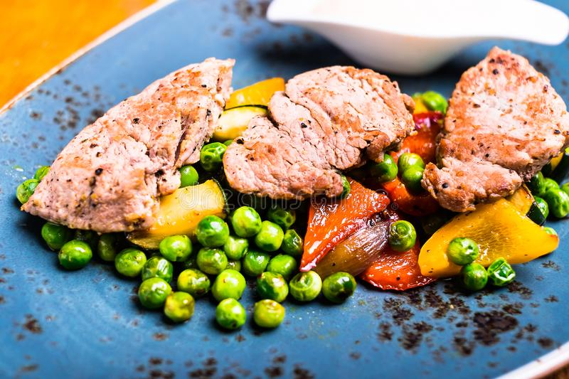 Easter food. Picnic food. Grilled pork meat fillet steaks lying on the mix of roasted vegetables - zucchini, eggplant, bell pepper. Frozen peas, top view royalty free stock photography