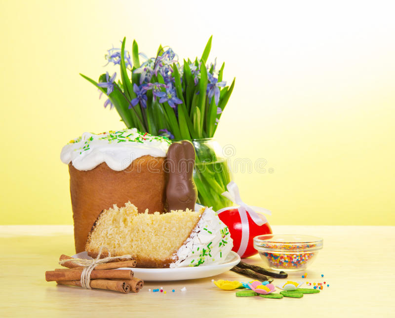 Easter food and vase with the flowers on a table. On a yellow background stock image