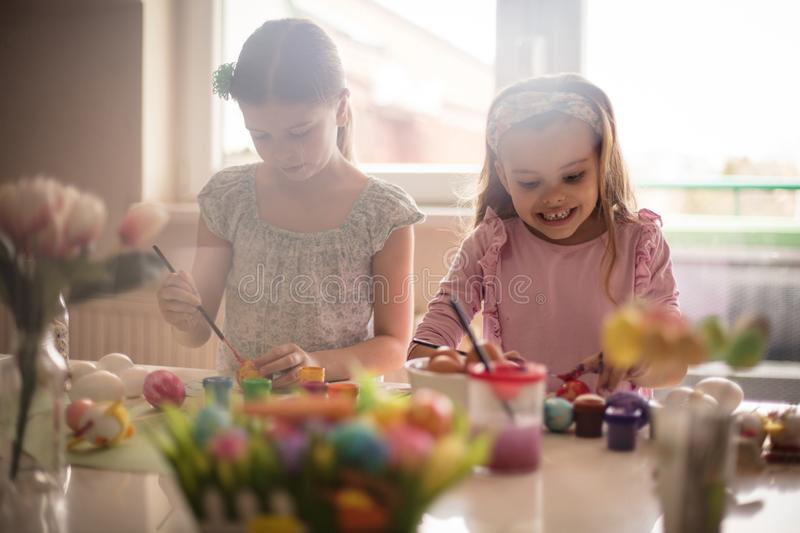 Easter is full of warm colors. Little girls coloring Easter egg royalty free stock photo