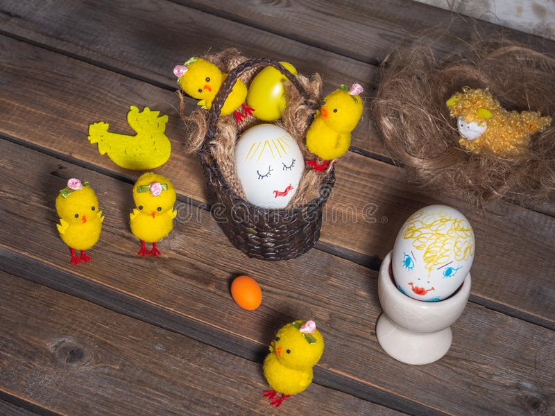 Easter fun picture with painted faces on the eggs, toy chickens are located on a wooden old background royalty free stock images