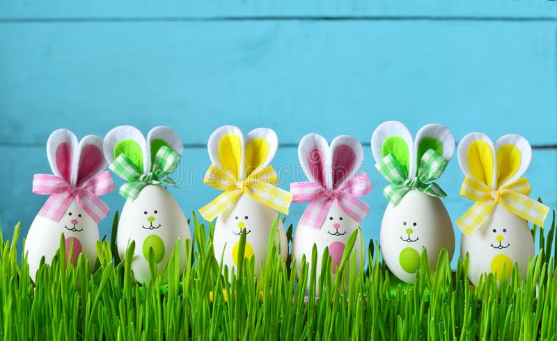 Easter funny bunny on green grass with easter eggs. Easter background. Easter funny bunny on green grass and easter eggs. Easter background stock image