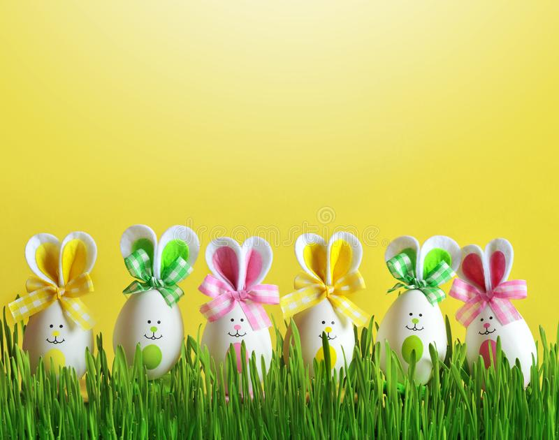 Easter funny bunny on green grass with easter eggs. Easter background. Easter funny bunny on green grass and easter eggs. Easter background royalty free stock image